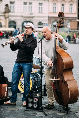 perform: PRAGUE, CZECH REPUBLIC - OCTOBER 10, 2014: Street Busker performing jazz songs at the Old Town Square in Prague. Busking is legal form of earning money on Prague Streets.