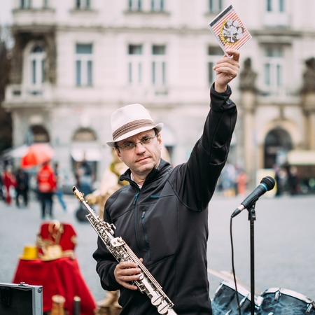 busker: PRAGUE, CZECH REPUBLIC - OCTOBER 10, 2014: Street Busker performing jazz songs at the Old Town Square in Prague. Busking is legal form of earning money on Prague Streets.