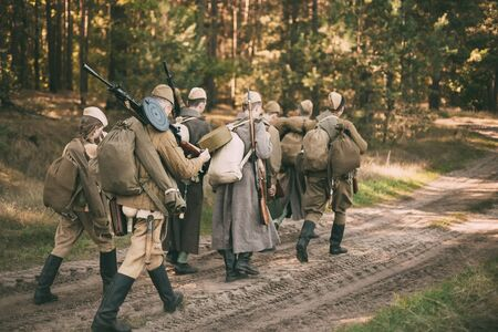 reenaction: Group of unidentified re-enactors dressed as Soviet russian soldiers goes along forest road. Stock Photo