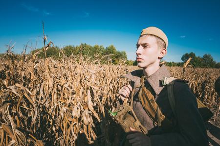 reenaction: Teryuha, Belarus - October 3, 2015: Unidentified re-enactor dressed as Soviet russian soldier goes along field road.