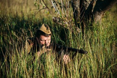 reenactor: Teryuha, Belarus - October 3, 2015: Unidentified re-enactor dressed as Soviet russian soldier aiming a machine gun at enemy Editorial