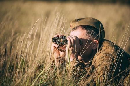 reenactor: Unidentified re-enactor dressed as Soviet soldier looks at an old army binoculars.