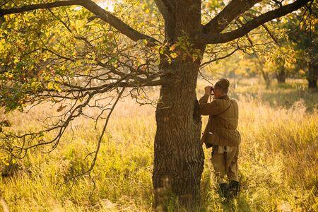 reenactor: Unidentified re-enactor dressed as Soviet soldier looks at an binoculars.