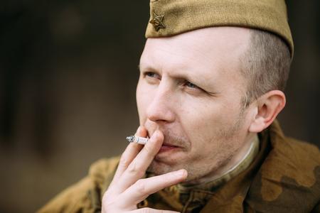 reenaction: PRIBOR, BELARUS - April, 04, 2015: Smoking unidentified re-enactor dressed as Russian Soviet soldier in camouflage