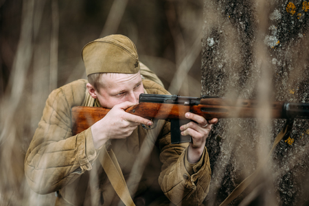 reenactor: PRIBOR, BELARUS - April, 04, 2015: Unidentified re-enactor dressed as Soviet russian soldier aiming a rifle at enemy