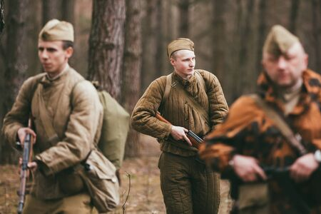 greatcoat: PRIBOR, BELARUS - April, 04, 2015: Group of unidentified re-enactors dressed as Russian Soviet soldiers in camouflage walks through forest