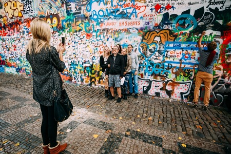 john lennon: Prague, Czech Republic - October 10, 2014: People walking and taking photo in famous place in Prague - The John Lennon Wall. Wall filled with Lennon inspired graffiti and lyrics from Beatles songs