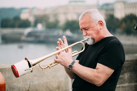 busker: Prague, Czech Republic - October 10, 2014: Street Busker performing jazz songs at the Charles Bridge in Prague. Busking is legal form of earning money on Prague Streets.