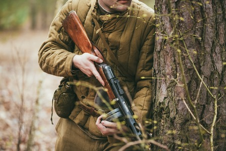 greatcoat: Unidentified re-enactor dressed as Russian Soviet soldier in camouflage in forest Stock Photo