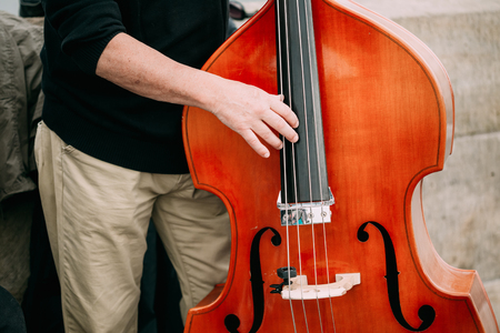 busker: Street Busker performing jazz songs outdoors. Close up of musical instrument contrabass Stock Photo