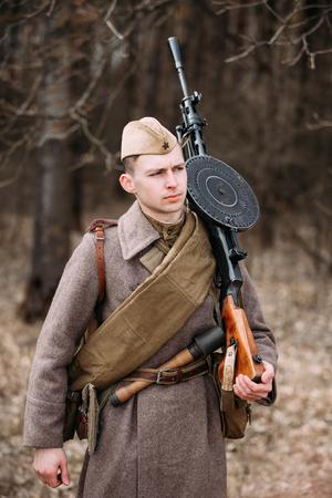 reenaction: PRIBOR, BELARUS - April, 04, 2015: Unidentified re-enactor with machine gun dressed as Russian Soviet soldier in camouflage