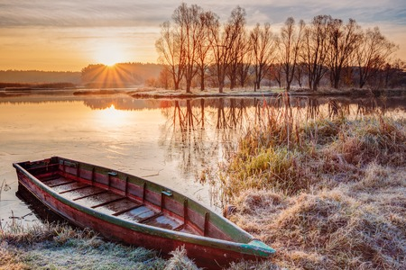 Calm Water Of Lake, River and rowing fishing boat at beautiful sunrise in autumn morning.