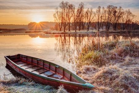 Kalme water van het meer, de rivier en roeien vissersboot op mooie zonsopgang in de herfst 's ochtends.
