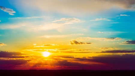 The sun shining over field. Bright Sun, Sunset, Sunrise. Colorful Blue and Yellow Sky.