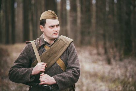 reenaction: PRIBOR, BELARUS - April, 04, 2015: Unidentified re-enactor dressed as Russian Soviet soldier in camouflage walk through forest
