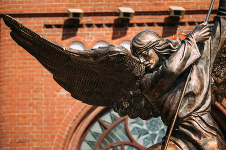 archangel: Statue Of Archangel Michael With Outstretched Wings, Thrusting Spear Into Dragon near Red Catholic Church Of St. Simon And St. Helena On Independence Square In Minsk, Belarus