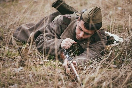 reloading: PRIBOR, BELARUS - April, 04, 2015: Unidentified re-enactor dressed as Soviet russian soldier reloading his rifle