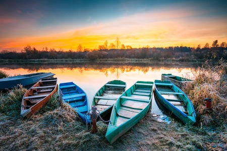 Lake, River and rowing fishing boat at beautiful sunrise in autumn morning. Old wooden boats and frosted grass. 스톡 콘텐츠