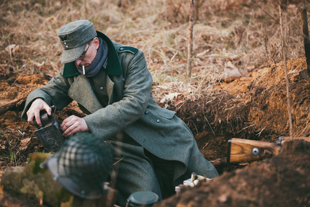 wehrmacht: PRIBOR, BELARUS - April, 04, 2015: Unidentified re-enactors dressed as german wehrmacht soldier in a trench settling for night