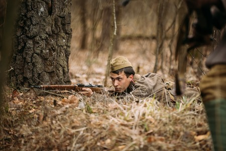 reenactor: PRIBOR, BELARUS - April, 05, 2015: Unidentified re-enactor dressed as Soviet russian soldier aiming a rifle at enemy in forest