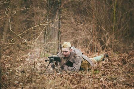 gunner: PRIBOR, BELARUS - April, 05, 2015: Unidentified re-enactor dressed as Soviet russian soldier olled on ground with a machine gun