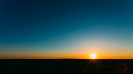 panoramic sky: Sunset, Sunrise, Sun Over Rural Countryside Field. Bright Clear Sky And Dark Ground. Panoramic View Stock Photo