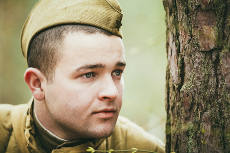 reenaction: PRIBOR, BELARUS - April, 05, 2015: Unidentified re-enactor dressed as Russian Soviet soldier in camouflage in forest
