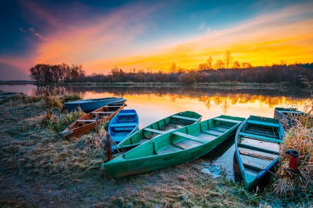 River and rowing fishing boat at beautiful sunrise in autumn morning. Old wooden boats and frosted grass.
