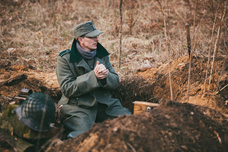settling: PRIBOR, BELARUS - April, 04, 2015: Unidentified re-enactors dressed as german wehrmacht soldier in a trench settling for night