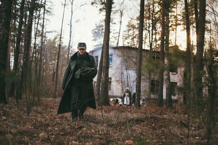 wehrmacht: PRIBOR, BELARUS - April, 04, 2015: Unidentified re-enactors dressed as german wehrmacht soldier walk in forest Editorial
