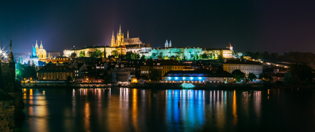 Night panoramic view of Prague cityscape, Czech Republic. Castle, St. Vitus Cathedral. Panorama of Lesser Town, Reflection in Vltava River