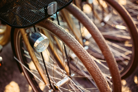 Row of parked vintage bicycles bikes for rent on sidewalk. Close up of wheel and bicycle headlight