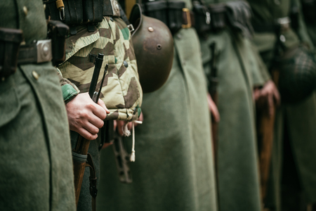 wehrmacht: Close up of german military ammunition of a German soldier. Unidentified re-enactors dressed as World War II German soldiers standing order.