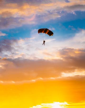 picada: Paracaidista En Paracaídas Colorido En Sunny Sunset Amanecer Cielo. Estilo de vida activo