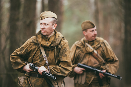 reenaction: PRIBOR, BELARUS - April, 04, 2015: Two unidentified re-enactors dressed as Russian Soviet soldiers in camouflage walks through forest