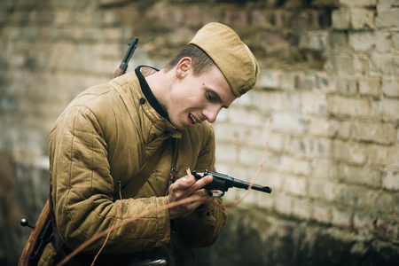 reenactor: PRIBOR, BELARUS - April, 05, 2015: Unidentified re-enactor dressed as Soviet russian soldier reloads gun
