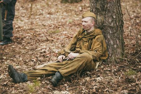 reenaction: PRIBOR, BELARUS - April 05, 2015: Young unidentified re-enactor dressed as Soviet soldier in overcoat resting under tree Editorial