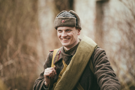 greatcoat: PRIBOR, BELARUS - April 05, 2015: Smiling unidentified re-enactor dressed as Russian Soviet soldier in overcoat Editorial