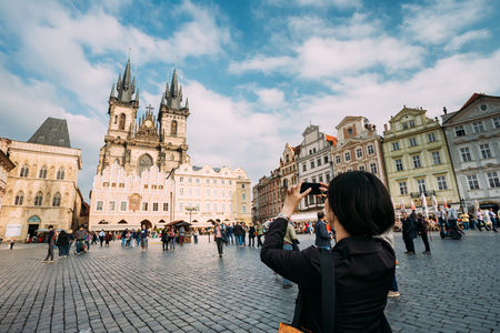 town square: Prague, Czech Republic - October 13, 2014: Tourist woman photographs the Church Of Our Lady Before Tyn In Old Town Square on your smartphone Editorial