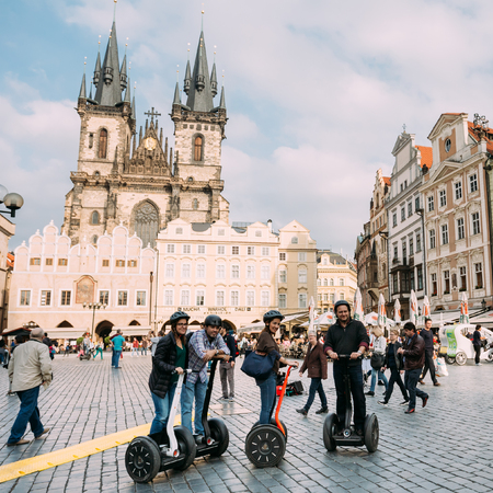 old town square: Prague, Czech Republic - October 13, 2014: Tourist rides a electric scooter Segway on old square on background of the Church Of Our Lady Before Tyn In Old Town Square