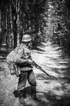 Unidentified re-enactor dressed as German soldier with rifle standing on road in woods. Black and white colors