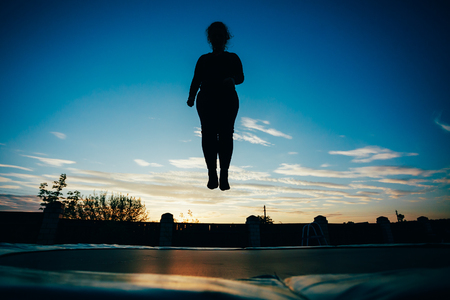 Silhouette Of Beautiful Plus Size Young Woman Girl Jumping On Trampoline On Evening Blue Sky Background