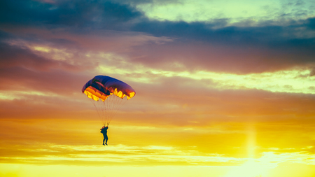 Skydiver Op Kleurrijke Parachute In Sunny Sunset Sky. Active Hobbies