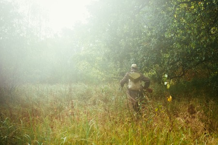 re enactment: Unidentified re-enactor dressed as World War II Soviet russian soldier running with machine gun in foggy forest grass Stock Photo