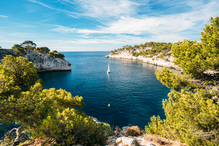 azure coast: Beautiful nature of Calanques on the azure coast of France. Calanques - a deep bay surrounded by high cliffs. Boat leaves from bay to open sea.