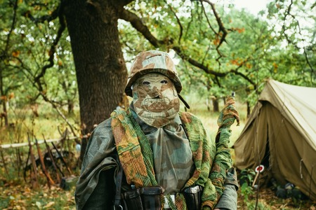 re enactment: Hidden unidentified re-enactor dressed as World War II german wehrmacht sniper soldier in forest.