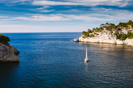 azure coast: Beautiful nature of Calanques on the azure coast of France. Calanques - a deep bay surrounded by high cliffs. Yacht boat leaves from bay to open sea. Stock Photo