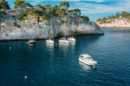 azure coast: White Yachts boats in bay. Calanques - a deep bay surrounded by high cliffs in the azure coast of France