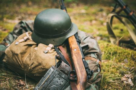 re enaction: German military ammunition of World War II on ground. Military helmet, lights, rifle