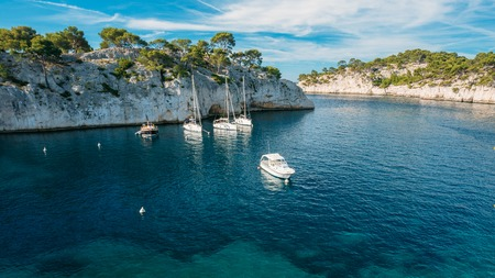 azure coast: White Yachts boats in bay. Panorama of Calanques - a deep bay surrounded by high cliffs in the azure coast of France. Panorama